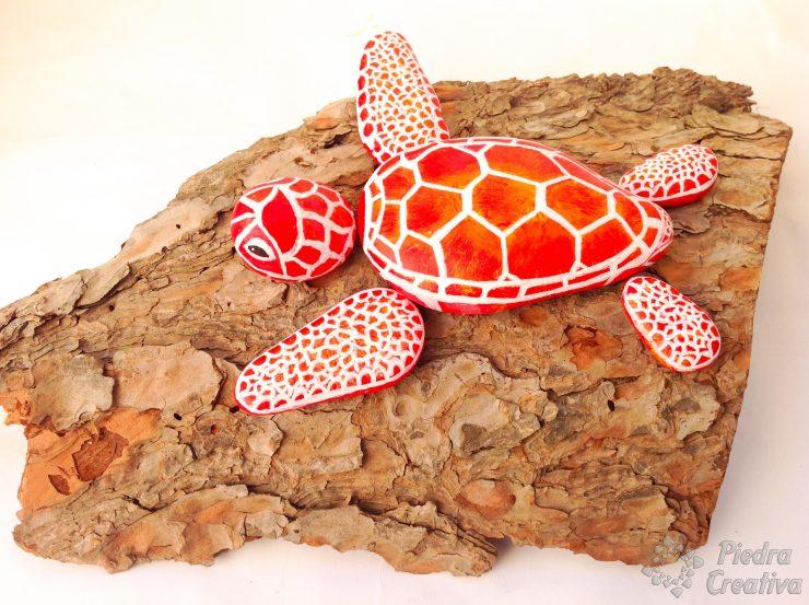 manualidad de tortuga pintada en piedras rojas